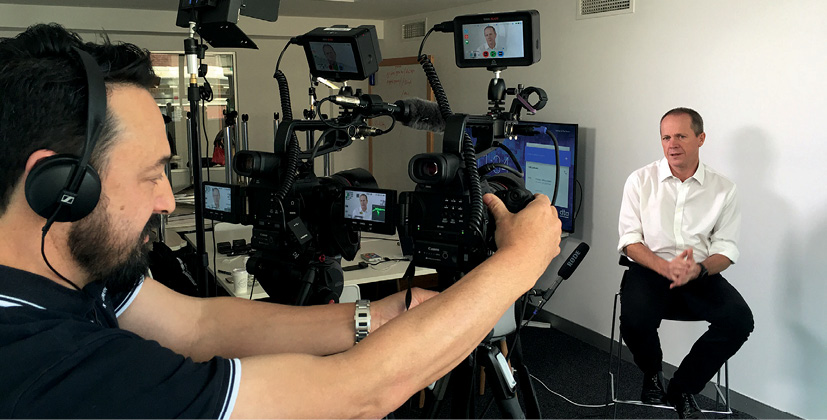 A video camera operator controlling a series of cameras and wearing headphones films Chief Executive Officer Gavin Slater.