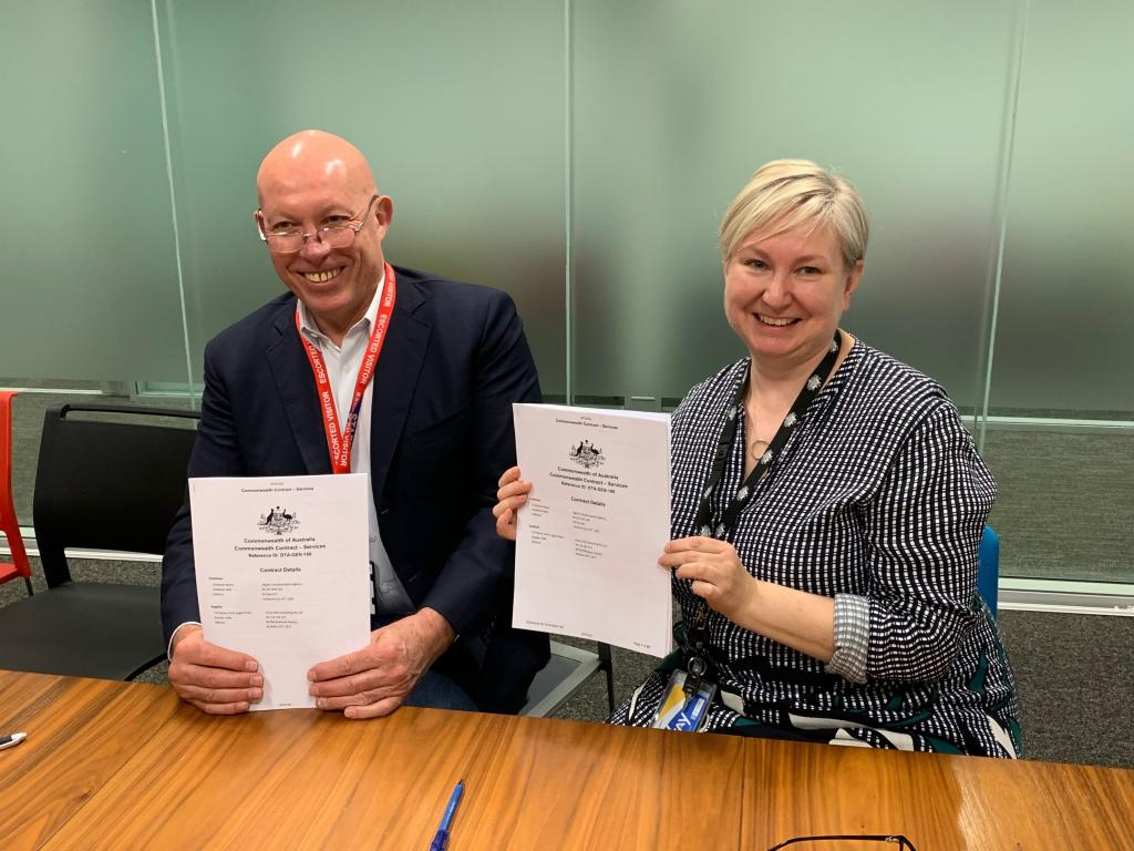 Ethos CRS Director Chas Savage and Style Manual Engagement Lead Susan Baird smile as they hold signed contracts