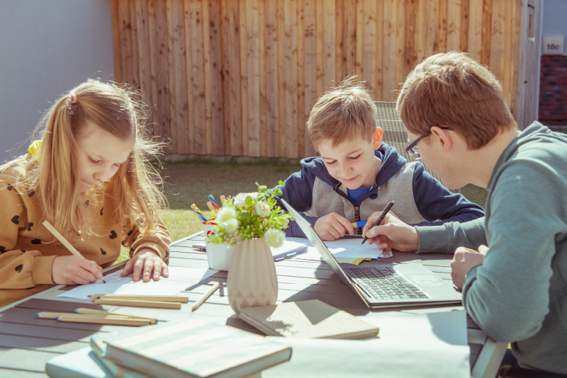 family of parent and two children outside working and playing at a table