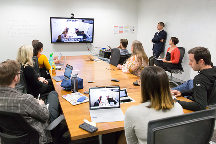 10 people sitting around a table on a video conference meeting with a team on screen.