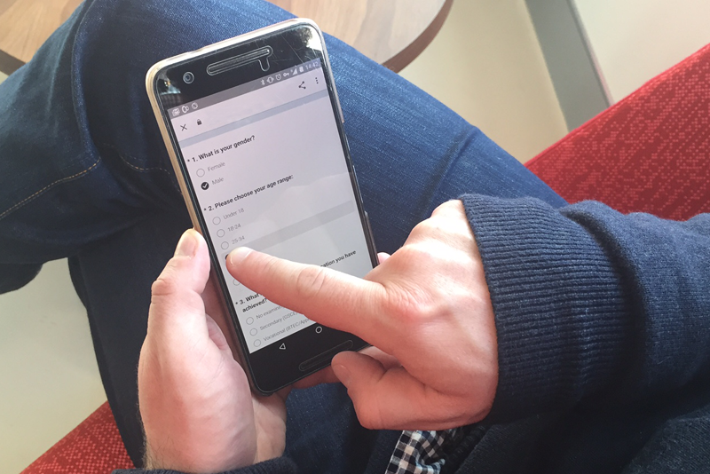 A user filling out a survey on a smart phone.