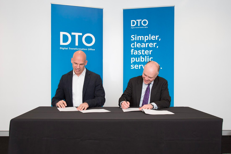DTO CEO Paul Shetler and the Chief Technology Officer HM Government signing the MOU in front of DTO banners.