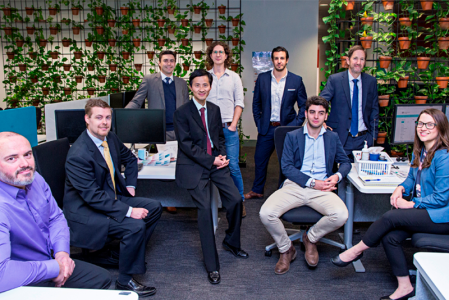 A group of men and women in business attire standing and sitting in front of a wall covered in flowering plants.