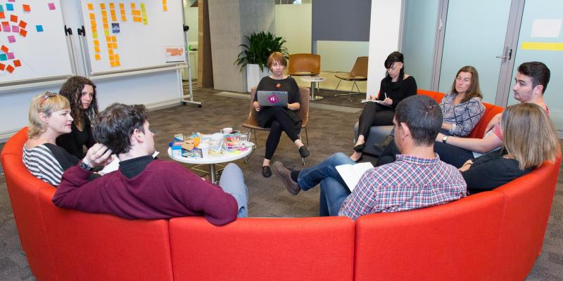A group of people sitting on red chairs discussing research findings.