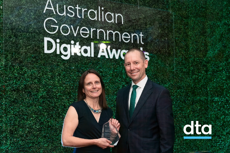 The CEO of the DTA and the winner of the award stand in front of a plant wall.