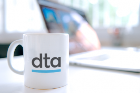 A white mug with 'DTA' written on it. In the background is a laptop.