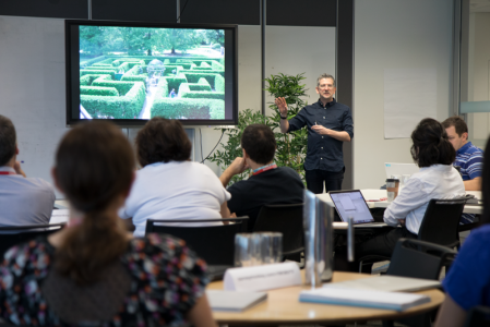 A presenter demonstrates the use of Google Analytics 360 in front of an audience. On a screen is a picture of a hedge maze.